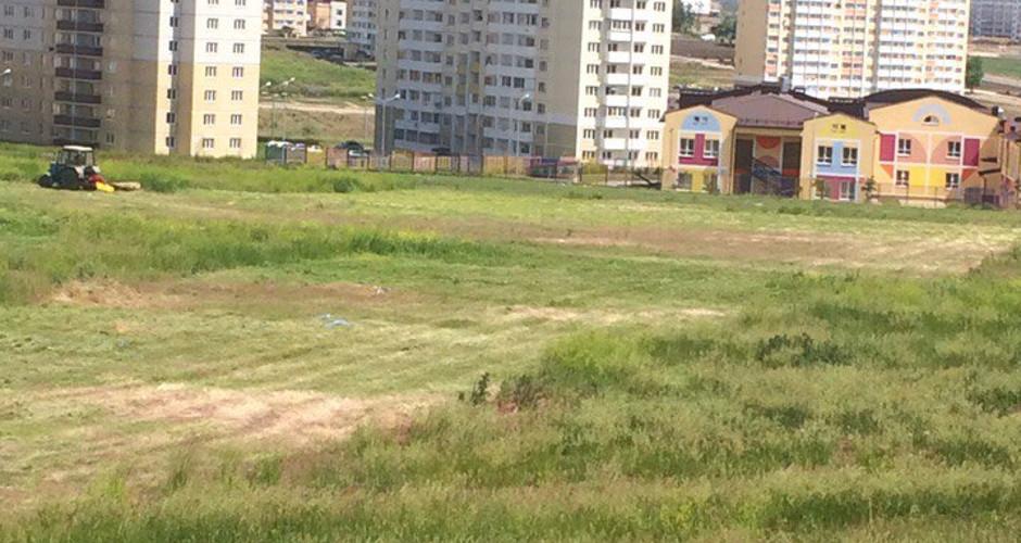 Косят траву для новой школы