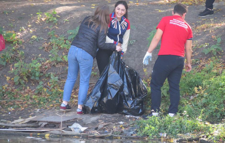 Девочки очищают русло реки Темерник от мусора